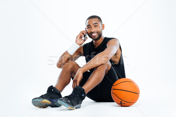 Happy man basketball player sitting and talking on cell phone Stock photo © deandrobot