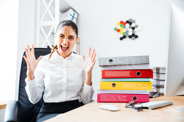 Angry crazy businesswoman screaming while sitting at workplace Stock photo © deandrobot