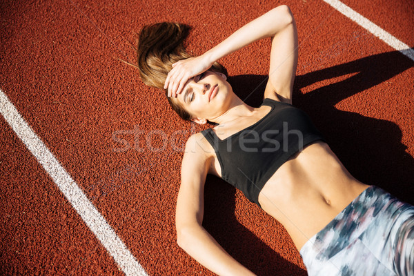 Fitness young woman laying on running track after workout Stock photo © deandrobot