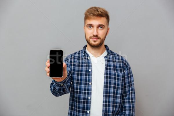 портрет улыбаясь бородатый человека смартфон Сток-фото © deandrobot