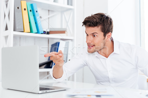 Angry annoyed businessman pointing finger at laptop Stock photo © deandrobot