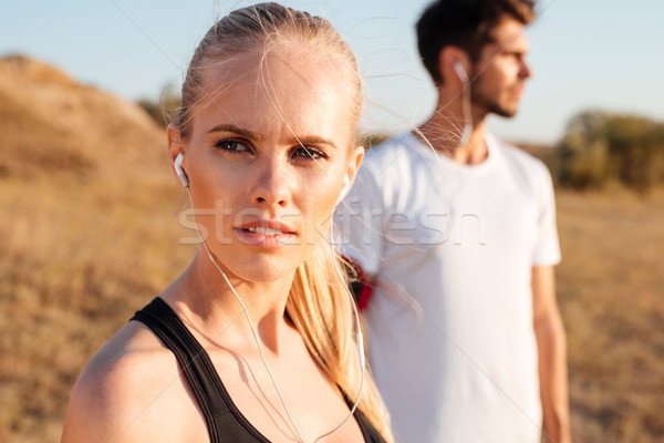 Beautiful young sports couple with earphones outdoors Stock photo © deandrobot