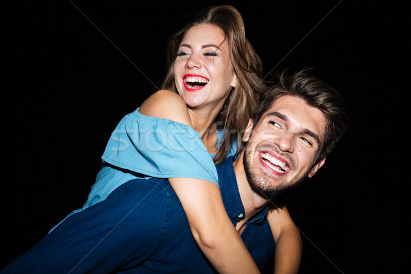 Smiling man holding girlfriend on his back at night Stock photo © deandrobot