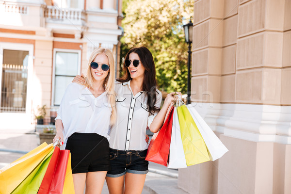 Happy women with shopping bags walking along city street Stock photo © deandrobot