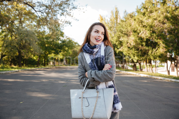 Happy young woman wearing scarf smiling and holding bag Stock photo © deandrobot