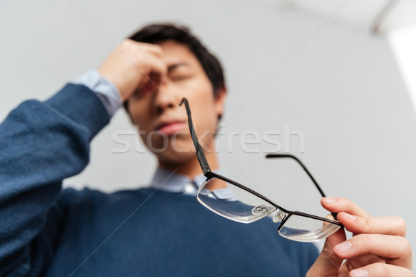 Image of tired asian man Stock photo © deandrobot