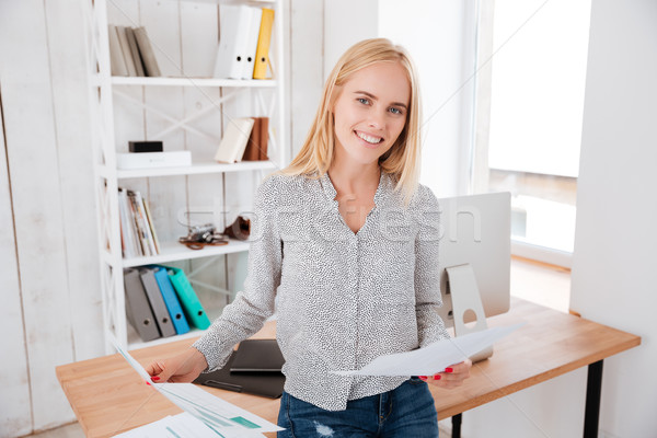 Attractive businesswoman holding documents and sitting on the office desk Stock photo © deandrobot
