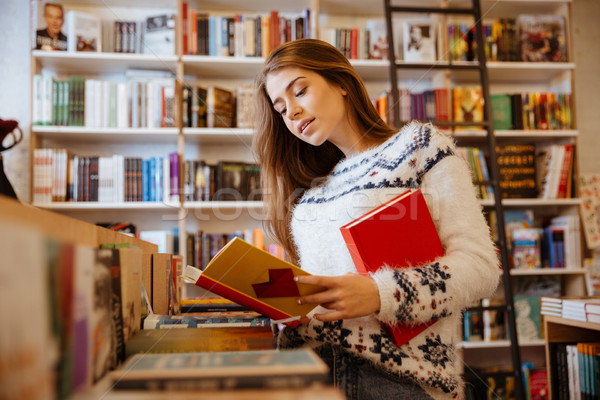 Beautiful brunette woman looking for a book in store Stock photo © deandrobot