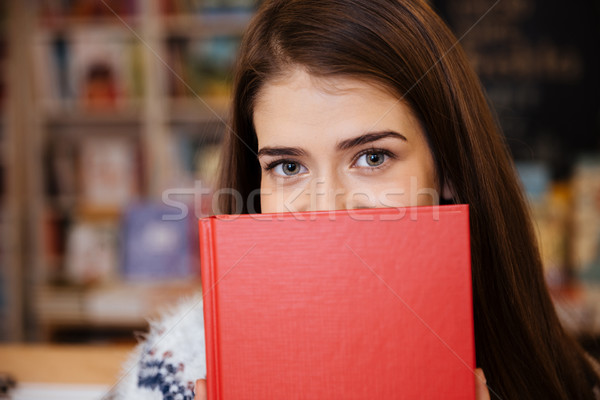 Portrait of a young woman covering her face with book Stock photo © deandrobot