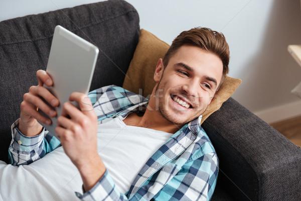 Mosolyog sörte férfi hazugságok kanapé táblagép Stock fotó © deandrobot