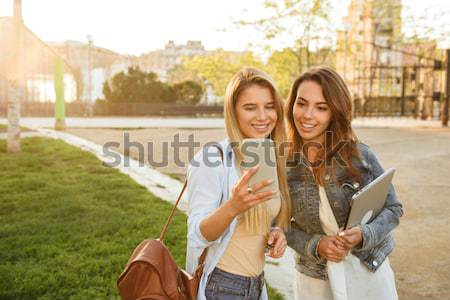 Two young smiling female classmates reading book outside the campus Stock photo © deandrobot