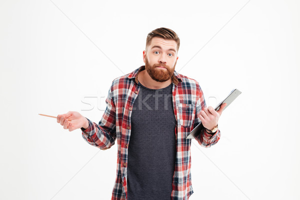 Portrait of a confused man shrugging shoulders and holding clipboard Stock photo © deandrobot