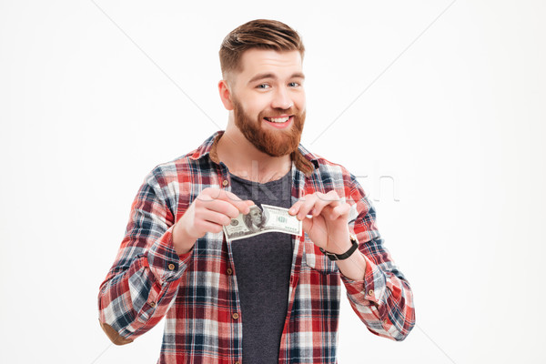 Young bearded man tearing US dollars banknotes Stock photo © deandrobot