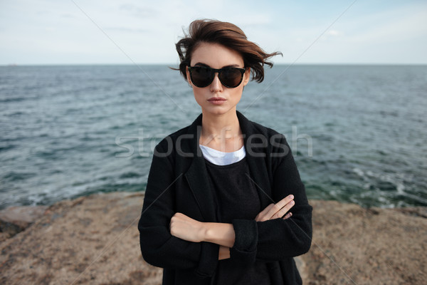 Woman in sunglasses standing with arms crossed on the seaside Stock photo © deandrobot