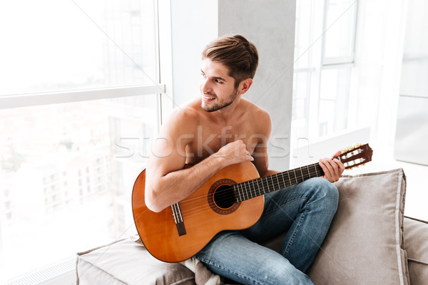 Shirtless man sitting and playing guitar at home Stock photo © deandrobot
