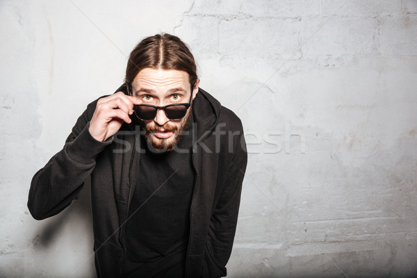 Young handsome bearded hipster man over wall background. Stock photo © deandrobot