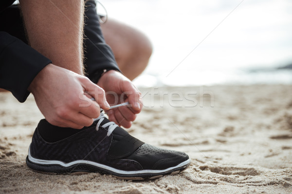 Man is tying shoelace while standing on the sand Stock photo © deandrobot