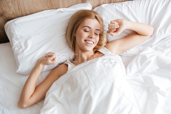 Top view of woman waking up after sleep Stock photo © deandrobot