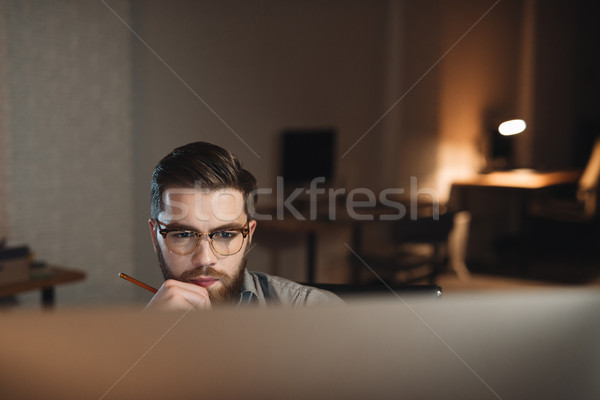 Bearded web designer looking to computer and working at night Stock photo © deandrobot