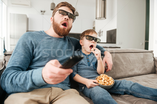 Confused father holding remote control while watching TV with son Stock photo © deandrobot