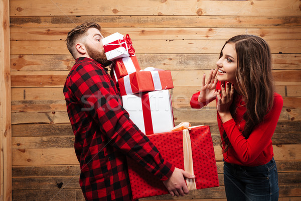 Young couple celebrating christmas with stack of heavy present boxes Stock photo © deandrobot