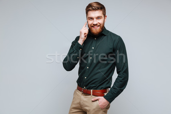 Smiling Bearded man in shirt talking on phone Stock photo © deandrobot