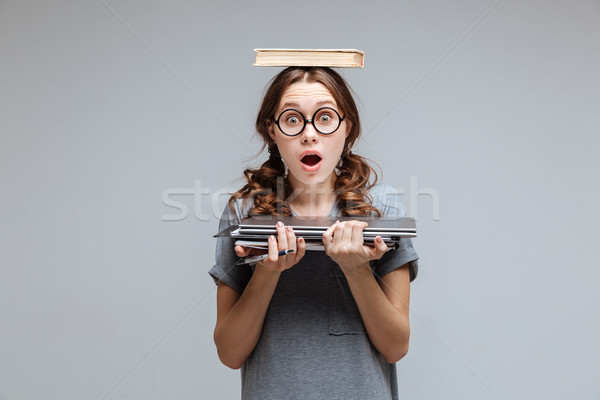 Surprised Female nerd with book on head Stock photo © deandrobot