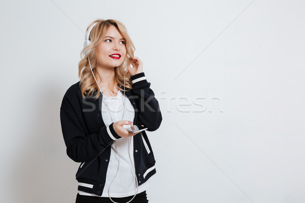 Smiling pretty woman with cell phone and earphones Stock photo © deandrobot
