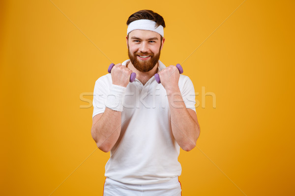 Happy sportsman with lightweight dumbbells Stock photo © deandrobot