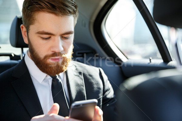 Serious bearded business man in suit looking at mobile phone in his hand Stock photo © deandrobot