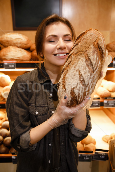 Smiling woman in supermarket choosing pastries Stock photo © deandrobot