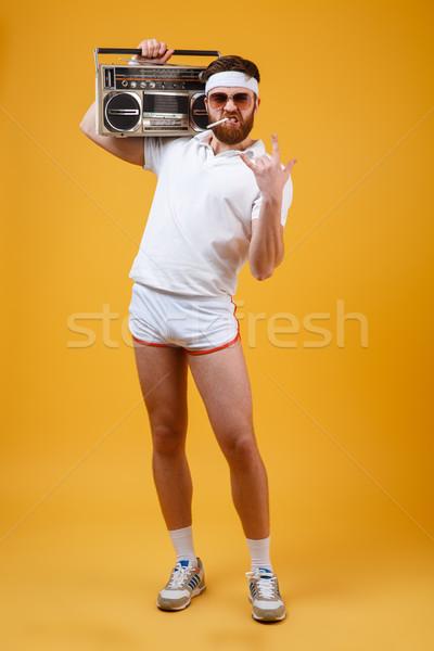 Serious man holding tape recorder make rock gesture. Stock photo © deandrobot