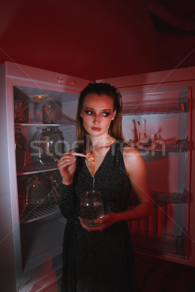Side view of calm woman holding doll and jar Stock photo © deandrobot