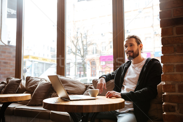 Sorridere barbuto uomo tavola laptop seduta Foto d'archivio © deandrobot