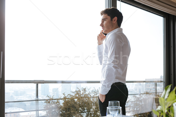 Handsome serious young man talking by mobile phone in cafe Stock photo © deandrobot