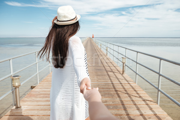 Follow me. Woman holding hand and leading friend on pier Stock photo © deandrobot