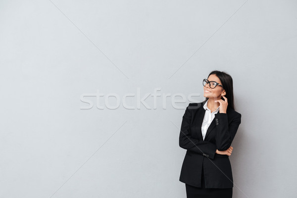 Business woman in eyeglasses thinking and looking away Stock photo © deandrobot