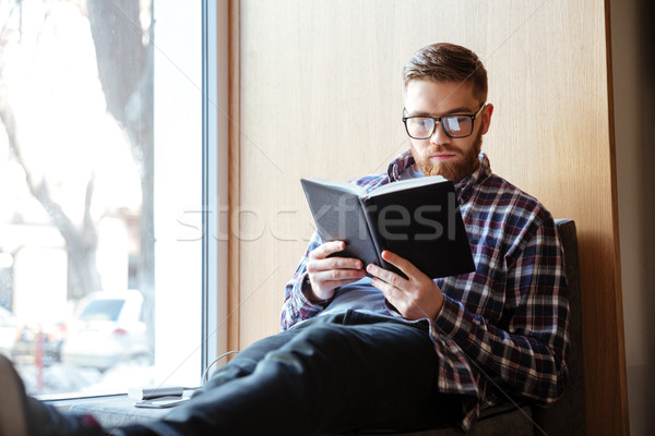 Student sitting on windowsill in library and reading book Stock photo © deandrobot