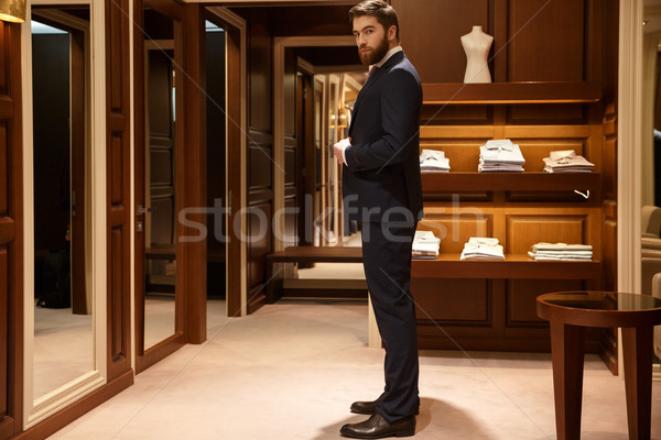 Side view of serious man tries on a suit Stock photo © deandrobot