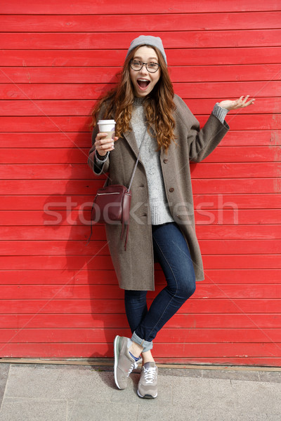 Woman drinking take away coffee and holding copyspace on palm Stock photo © deandrobot