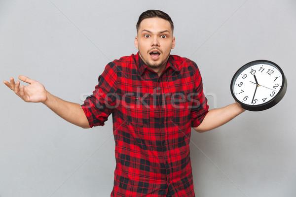Férfi tart óra póló néz kamera Stock fotó © deandrobot