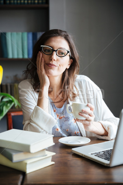 Bored mature woman in glasses holding cup of tea and looking at camera while sitting at the table wi Stock photo © deandrobot