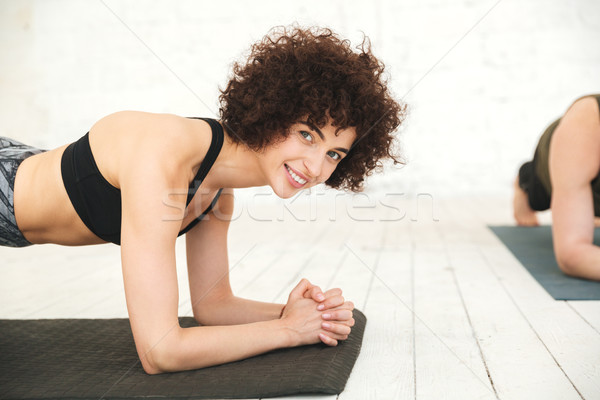Smiling fitness woman planking on an exercise mat Stock photo © deandrobot