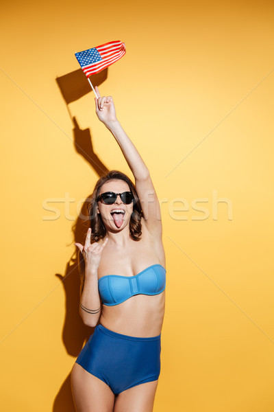 Smiling young woman in swimwear wearing sunglasses holding USA flag Stock photo © deandrobot