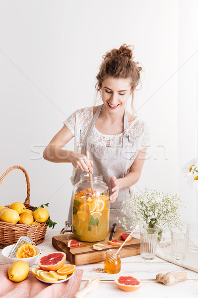 Concentrated woman standing indoors cooking citrus beverage Stock photo © deandrobot