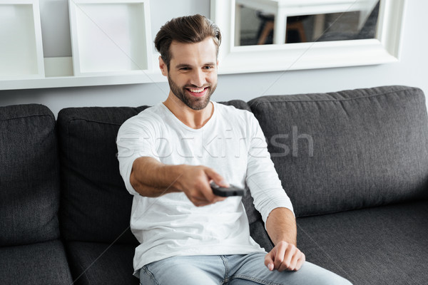 Young cheerful man sitting on sofa holding remote control. Stock photo © deandrobot