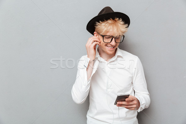 Cheerful caucasian man wearing glasses listening music Stock photo © deandrobot