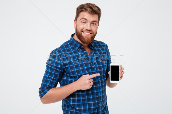 Smiling Bearded man in checkered shirt showing blank smartphone screen Stock photo © deandrobot