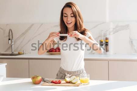 Smiling attractive woman taking a picture of fruit slices Stock photo © deandrobot