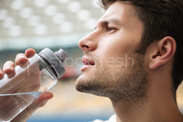 Close up profile portrait of a handsome man drinking water Stock photo © deandrobot